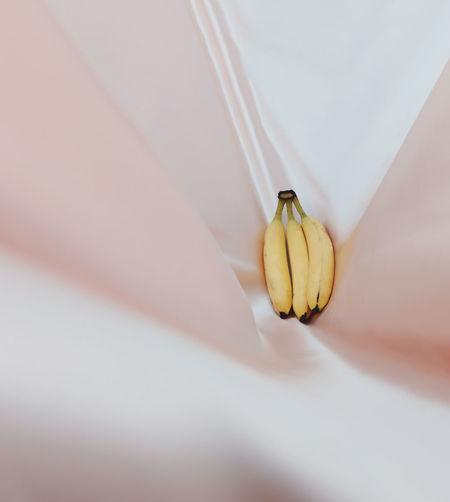 Close-up of banana on pink sheet
