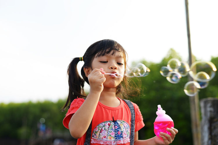 Girl blowing bubbles while standing against sky in park