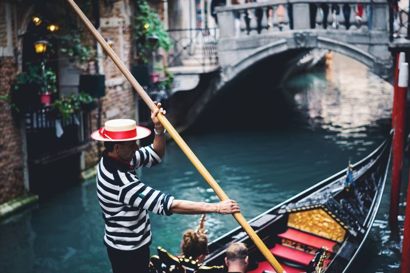 Side View Of Gondolier On Boat Sailing In Canal