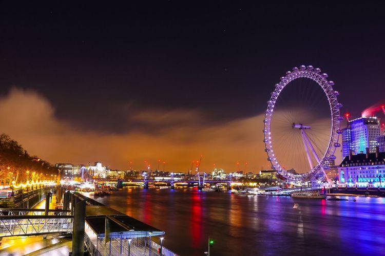 Illuminated Ferris Wheel Over River In City At Night
