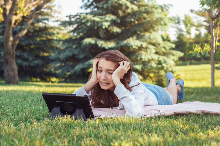 Worried young woman using tablet while lying on grass