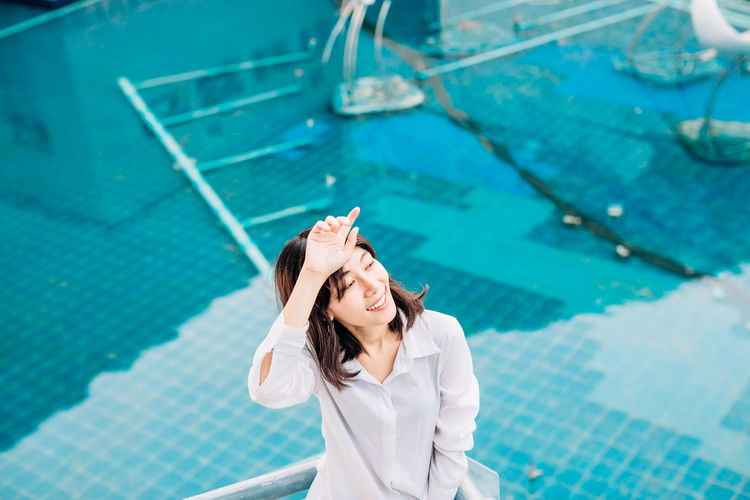 High angle view of woman standing at swimming pool