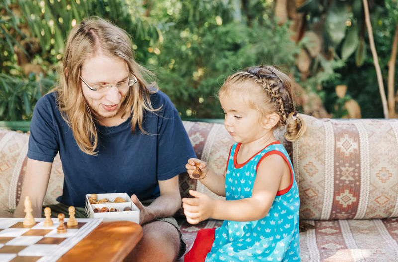 Father and daughter playing chess while sitting on sofa