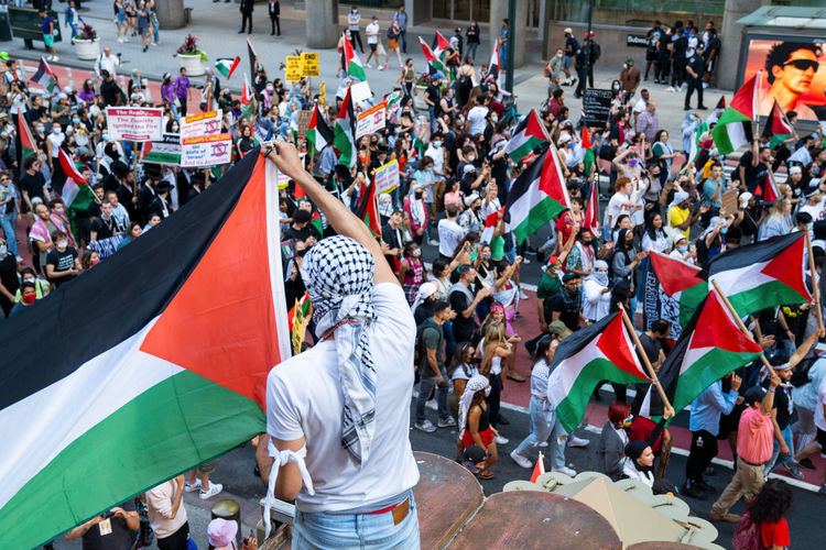 Palestinian flag held over a palestinian protest - day of rage. photographed june 15, 2021