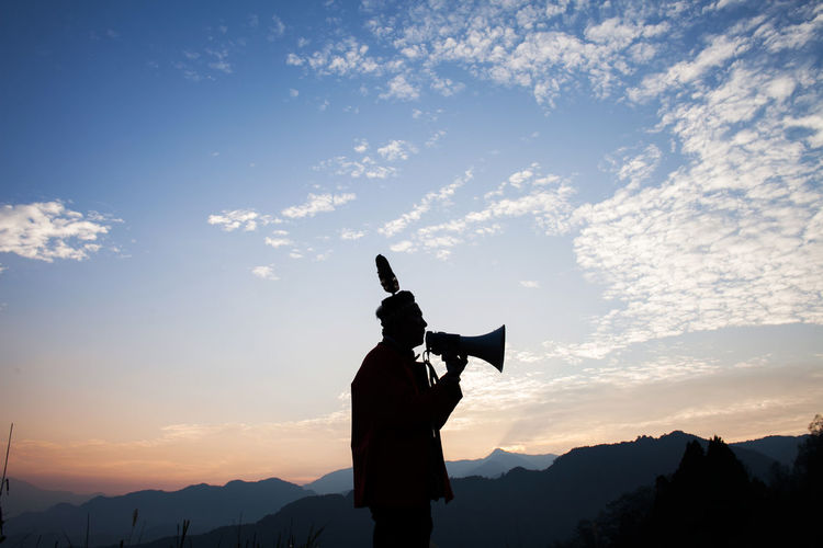 Silhouette man speaking on megaphone while standing against sky during sunset