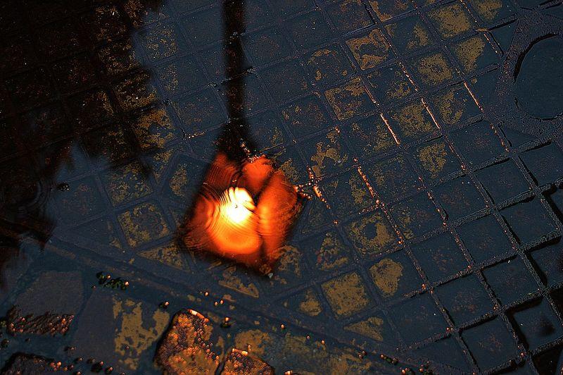 Reflection of illuminated street light on puddle at dusk