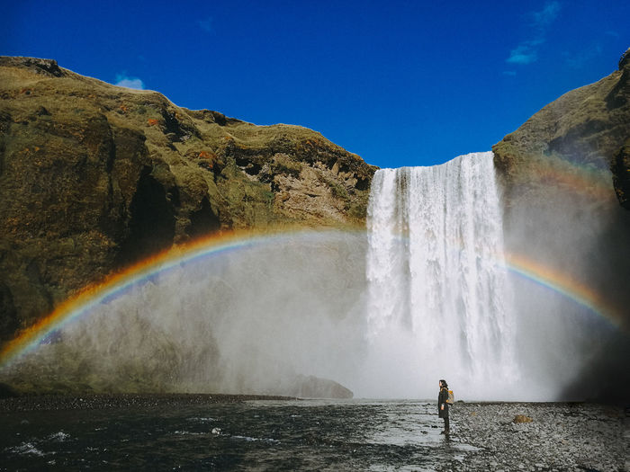 Scenic View Of Waterfall With Rainbow In Sky