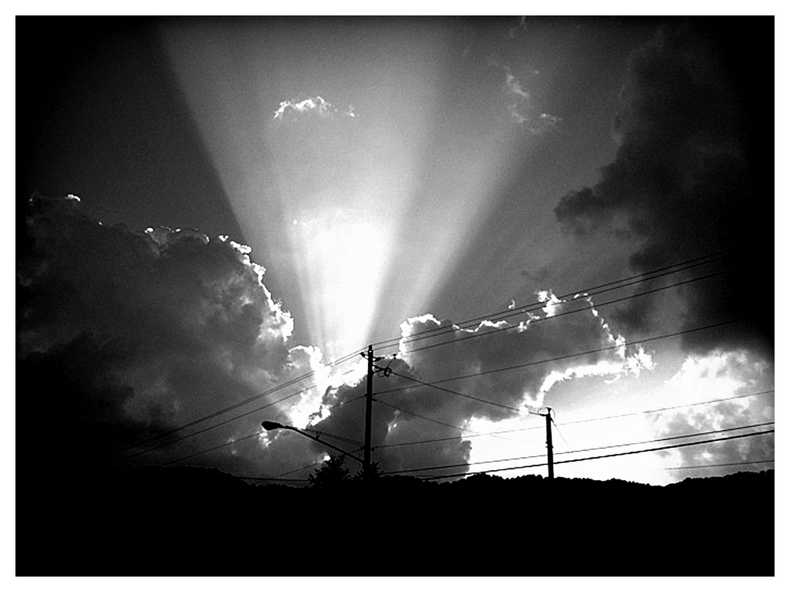 low angle view, transfer print, sky, electricity, night, silhouette, illuminated, auto post production filter, power line, lighting equipment, cloud - sky, street light, connection, electricity pylon, nature, outdoors, no people, beauty in nature, power supply, glowing