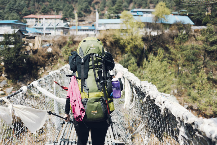 First rope bridge crossing. The Week on EyeEm Activity Adult Adventure Backpack Bridge Clothing Day Flags Focus On Foreground Hiking Leisure Activity Lifestyles Men Nature One Person Outdoors Plant Real People Rear View Three Quarter Length Village Walking Warm Clothing