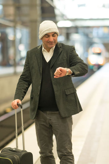 Smiling Mature Man With Suitcase Checking Time At Railroad Station Platform