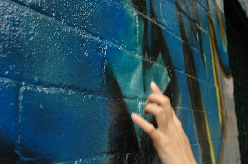 Close-up of person touching wall