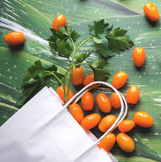 environmentally friendly packaging on green background Eco Product Environmental Farmer Paper Bag Shopping Bag Close-up Concept Eco Friendly Environment Flat Lay Food Food And Drink Freshness Healthy Eating Leaf Orange Color Plant Part Produce Raw Food Reusable Tote Vegetable Wellbeing Whire