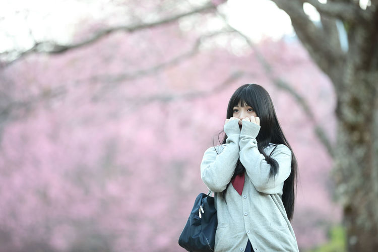 Young woman looking away while standing against pink flowering tree