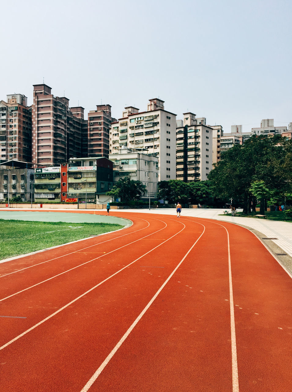 architecture, building exterior, clear sky, built structure, running track, day, outdoors, sport, tree, city, no people, sports track, sky