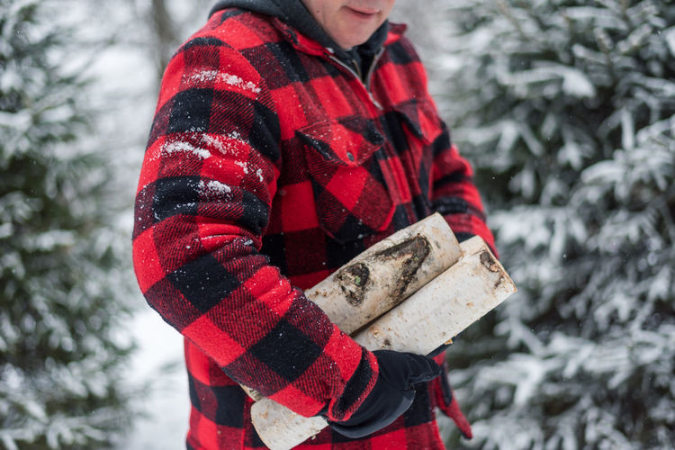 Midsection of person holding christmas tree during winter