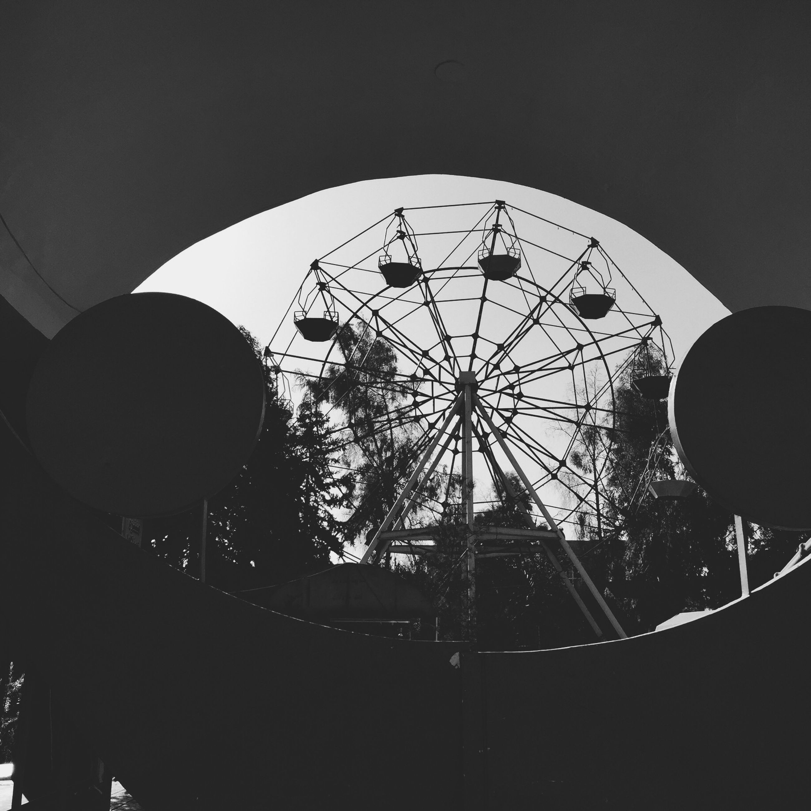 ferris wheel, low angle view, amusement park ride, amusement park, arts culture and entertainment, built structure, architecture, sky, circle, illuminated, clear sky, fun, famous place, travel destinations, travel, silhouette, geometric shape, sphere, night, outdoors