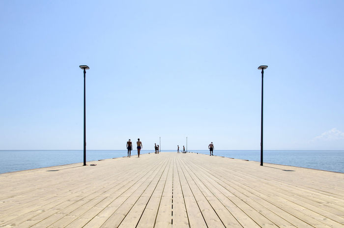 Water Sea Street Light Clear Sky Horizon Over Water Pier The Way Forward Tranquil Scene Tranquility In A Row Lighting Equipment Tourism Scenics Travel Destinations Long Day Calm Group Of People Jetty Blue