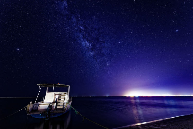 Boat Moored At Scenic Illuminated Sea Against Sky During Night