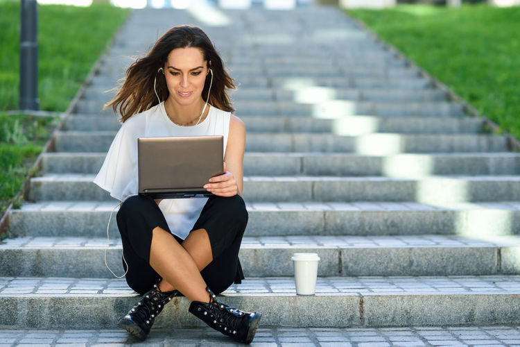 Beautiful young woman using laptop in city