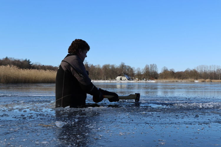 Side view of man sitting against lake against clear blue sky