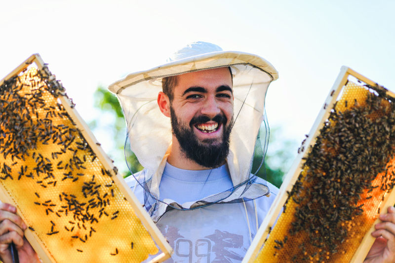 Young beekeeper works with bees in garden APIculture Farm HoneyBee Honeycomb Sunset_collection Work Worker Young Apiarist Bee Beekeeper Beekeeping Beeswax Colony Comb Hexagon Hive Honey Insect Inspecting Organic Food Pollen Portrait Product Summer