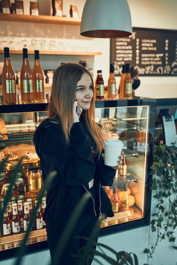 Woman standing by glass of store