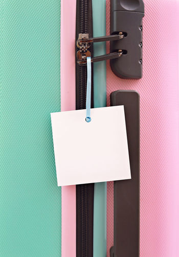 Suitcase with blank tag Claim Green Color Holiday Plane Travel Trip Vacations Aircraft Bag Baggage Clothing Insurance Label Luggage On Board Packing Personal Accessory Pink Color Protection Still Life Suitcase Tag Travel Insurance Voyage White Background
