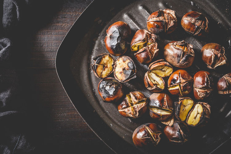 Roasted chestnuts in iron grilling pan over rustic wooden table. Top view. Autumn Chestnut Chestnuts Cooking Iron Meal Snack Brown Food Fried Fruit Gourmet Healthy Heap Ingredient Nut Opened Pan Roasted Roasting Seasonal Sweet Tasty Traditional Wooden