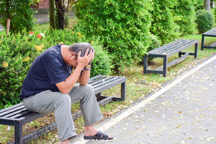 Frustrated man sitting on bench in park
