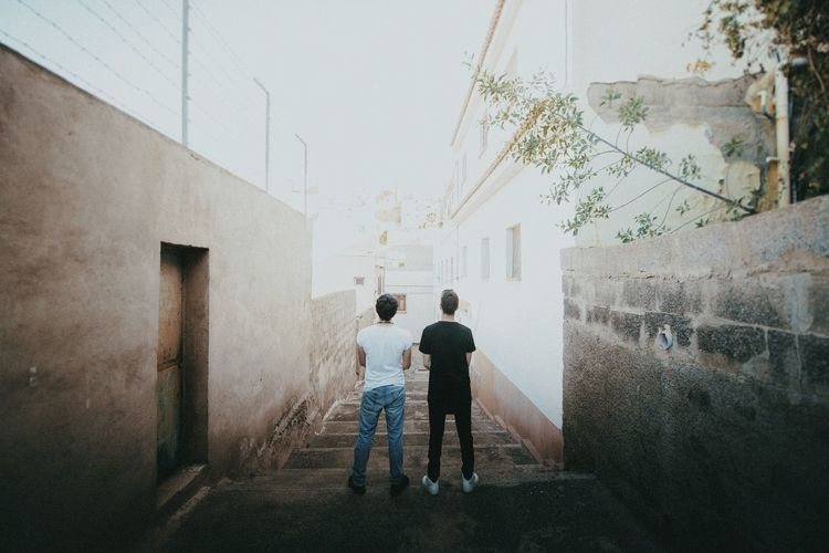 Rear view of two friends standing on staircase amidst wall