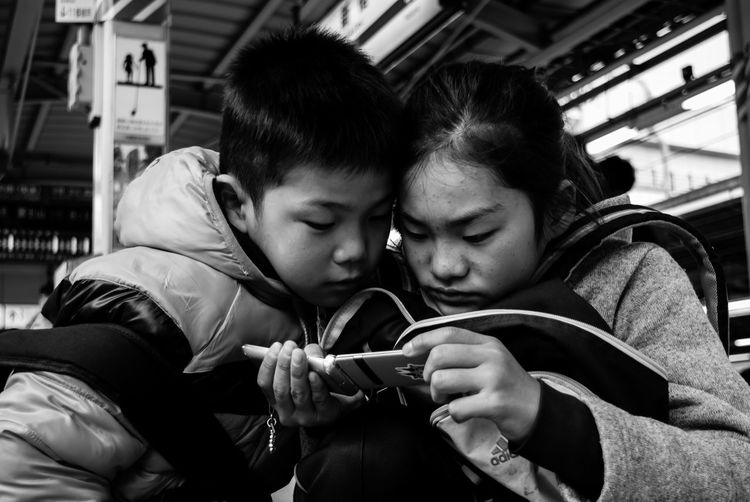 Siblings using mobile phone at railroad station platform
