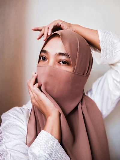 Portrait of a young woman covering face