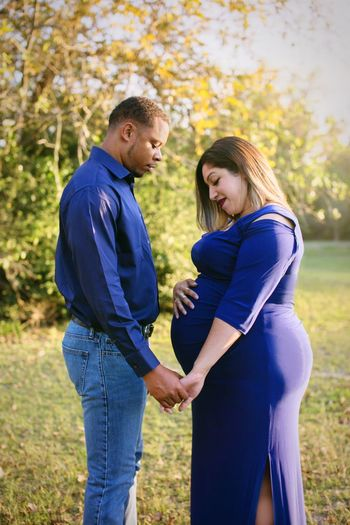 Pregnant woman with husband standing on lawn
