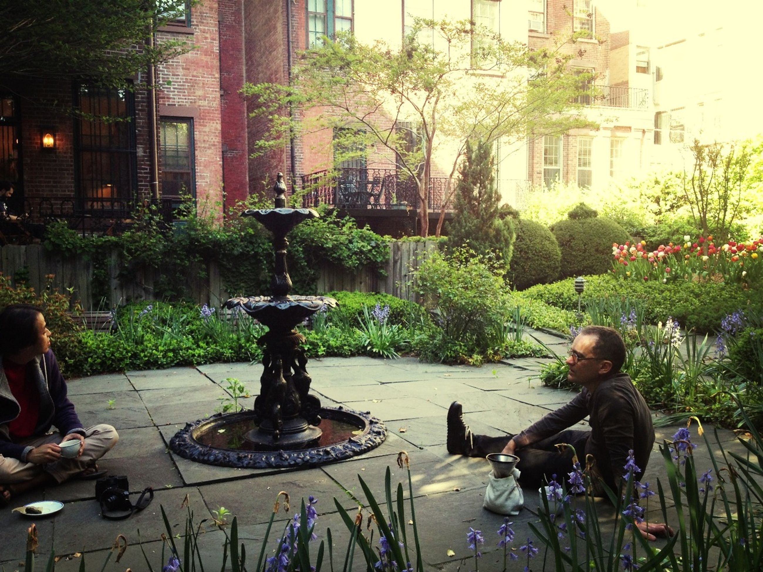 lifestyles, leisure activity, table, sitting, architecture, building exterior, built structure, tree, men, chair, casual clothing, person, potted plant, food and drink, holding, plant, day, incidental people