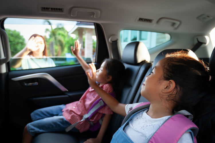 Mother waving hand to kids sitting in car