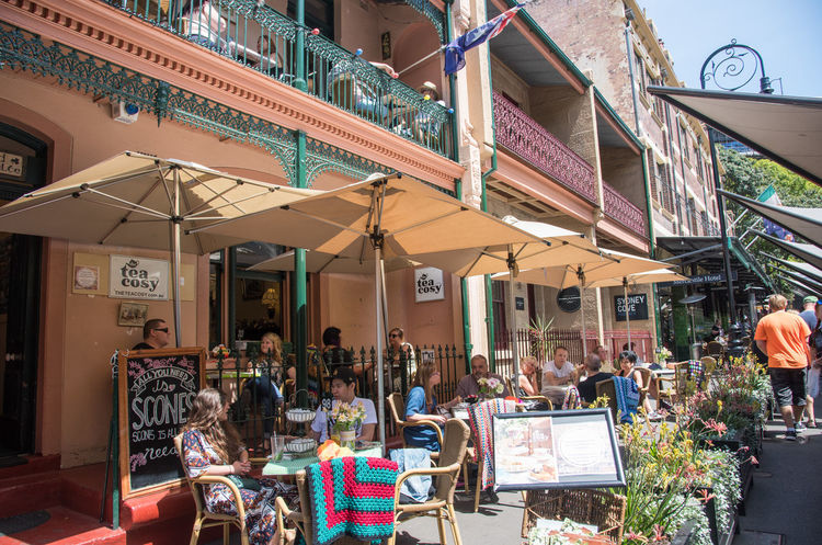Sydney,NSW,Australia-November 20,2016: People eating outdoors at The Tea Cosy with handmade blankets and the Rocks Market in Sydney, Australia Australia City Life Eating Market Menu Relaxing Sunny Tables And Chairs Tea The Rocks The Tea Cosy Blankets Break Building Cafe Chalkboard Group Handmade Sidewalk Cafe Social Gathering Socializing Sydney Togetherness Umbrella Weekend Activities