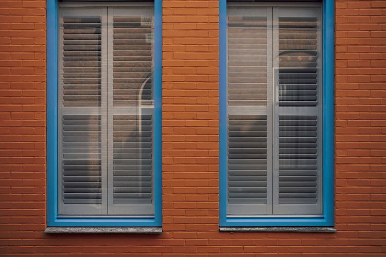 Blue framed window with blinds in red brick wall