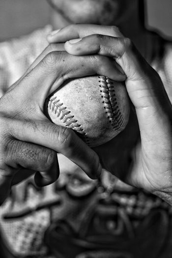 Close-up of man holding baseball ball in hand