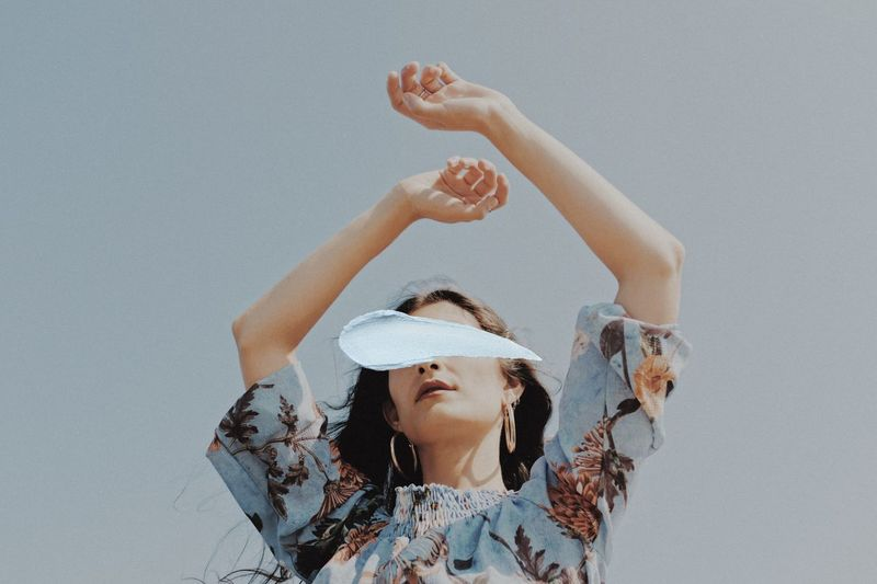 Low angle portrait of woman with arms raised against sky