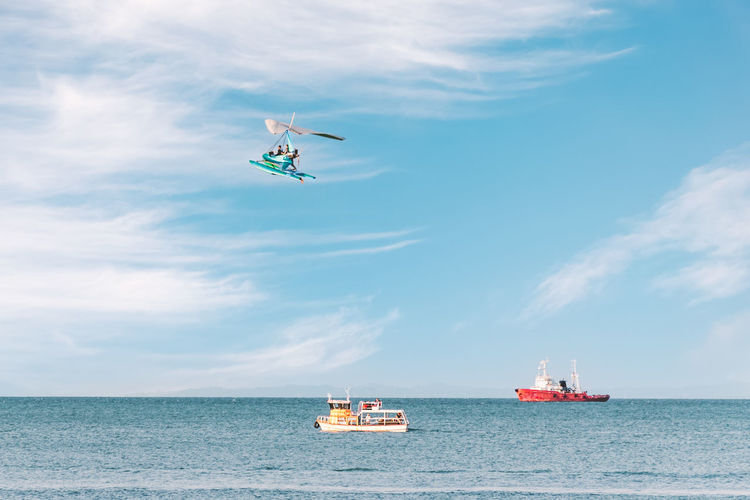Side view of the sea with pleasure ships and a flying paraglider. fun entertainment at the seaside