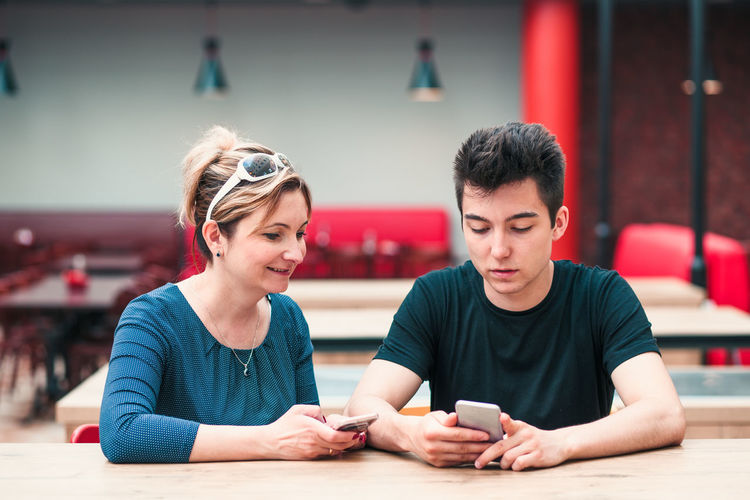 Mother and son using mobile phone at restaurant