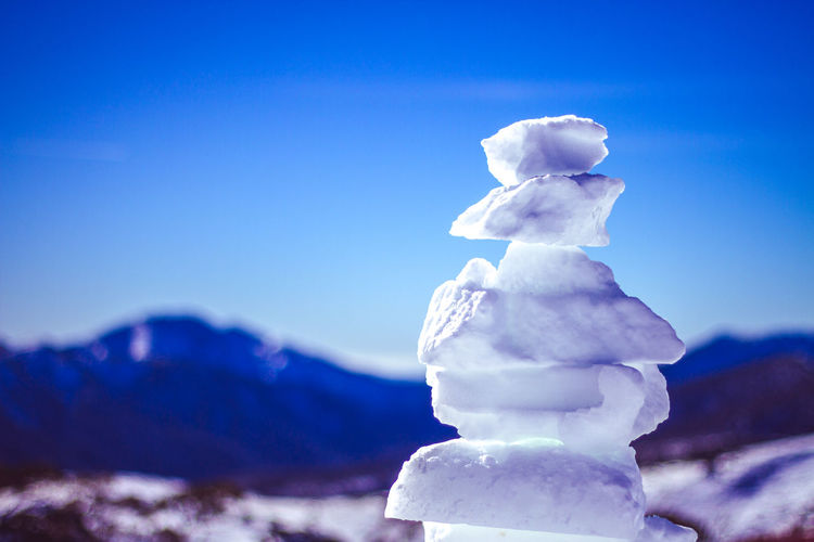 Close-up of snow on mountain against blue sky