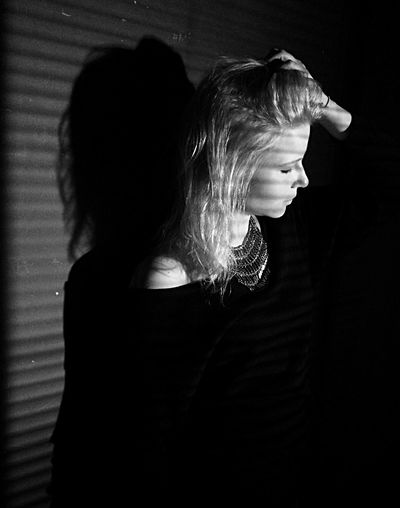 Young Woman Standing By Wall With Hand In Hair