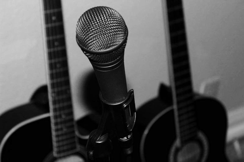 Close-Up Of Microphone Against Guitars