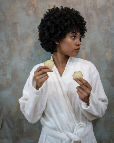 Woman eating food against wall