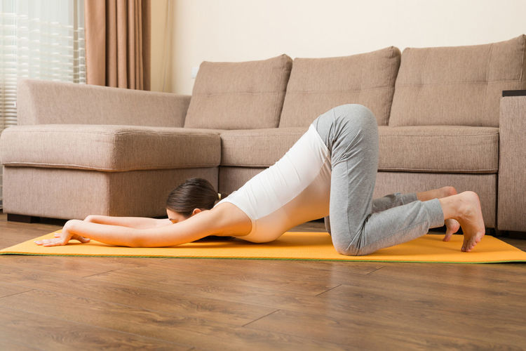 Midsection of woman lying on sofa at home