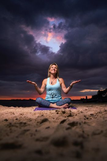Full length of smiling woman looking up while sitting at beach against storm clouds