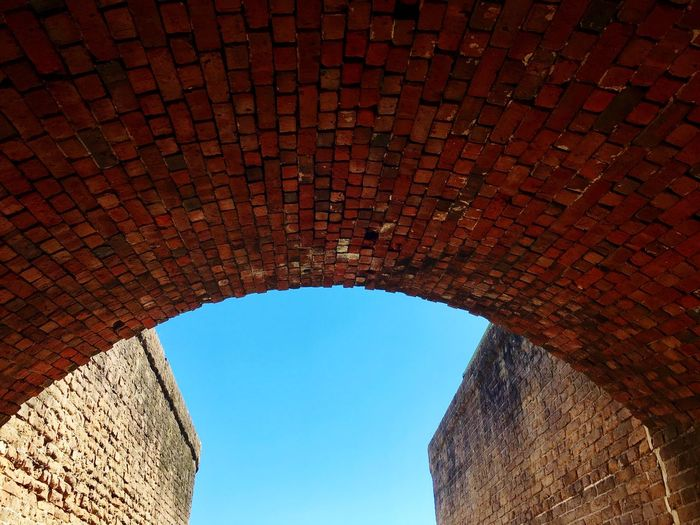Low angle view of brick wall against sky