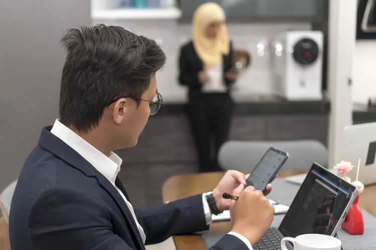 Asian malay man working at home with laptop Wireless Technology Technology Communication Business Well-dressed Connection Side View Focus On Foreground Men Adult Holding Office Young Adult Business Person Indoors  Businessman Mobile Phone Males  Real People Formalwear Coworker