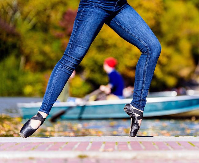 Low section of woman wearing ballet shoes dancing against boat on lake
